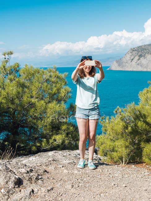 Giovane donna in pantaloncini utilizzando il telefono cellulare e scattare selfie in piedi sulla scogliera con alberi sullo sfondo del paesaggio marino blu — Foto stock