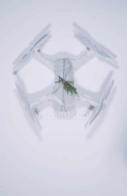 Беспилотник завернутый в рождественский подарок с еловой веткой на белом фоне — стоковое фото