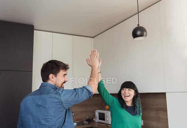 Веселый молодой человек и женщина дают друг другу пять, стоя вместе на современной кухне — стоковое фото