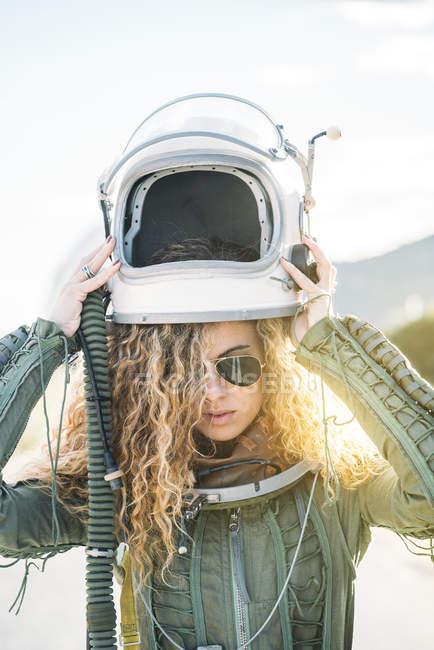 Mujer confiada en traje de astronauta que se pone el casco a la luz del sol - foto de stock