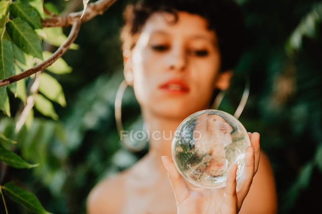 Топлесс брюнетка девушка держит стеклянный прозрачный шар в зеленых лесах — стоковое фото