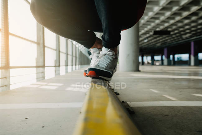 Close-up of male feet in sneakers walking on rail in building — Stock Photo
