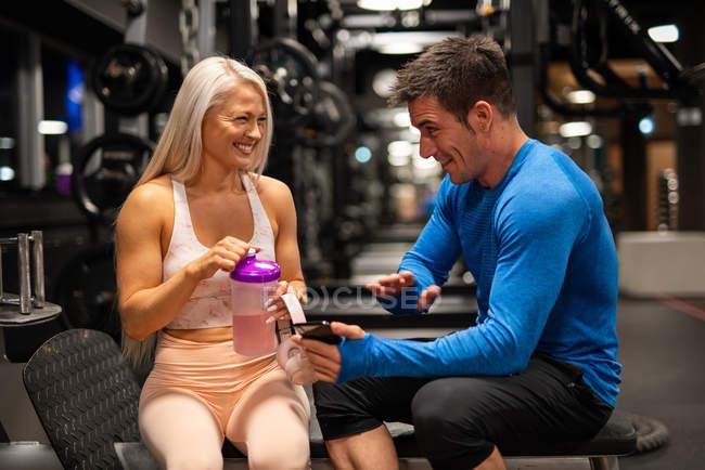 Веселый здоровый мужчина и женщина сидят в спортзале и смеются — стоковое фото