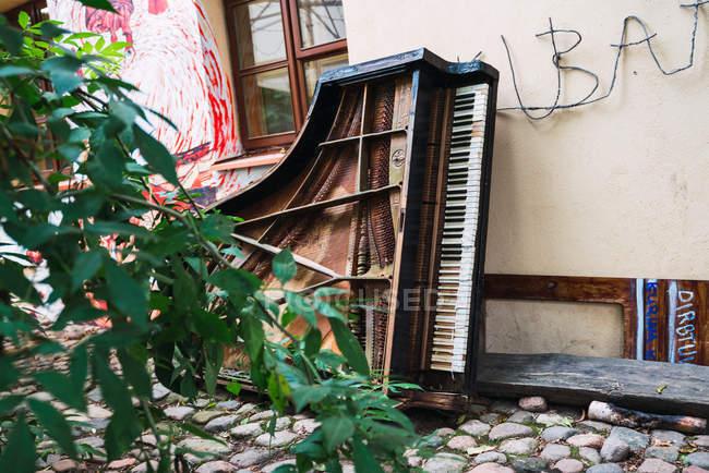 Broken piano près s'appuyant sur une chaussée de pierre de la rue de la petite ville de vieux — Photo de stock