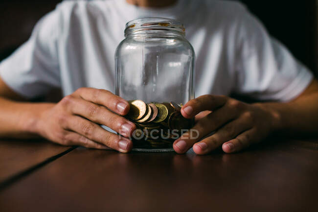 Unrecognizable guy holding glass jar with shiny coins while sitting at wooden table — Stock Photo