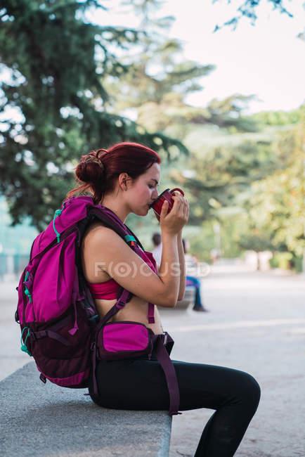 Молодая женщина в спортивной одежде с розовым рюкзаком сидит на скамейке в парке и пьет горячий чай из металлической чашки — стоковое фото