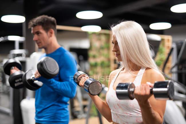 Атлетичные мужчина и женщина тренируются с гантелями в тренажерном зале — стоковое фото