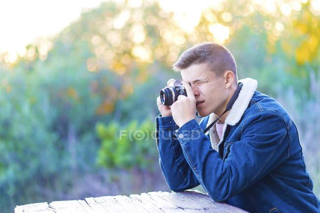 Jovem sentado à mesa ao ar livre com câmera fotográfica — Fotografia de Stock