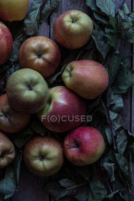 Fresh ripe apples and leaves on rustic table — Stock Photo