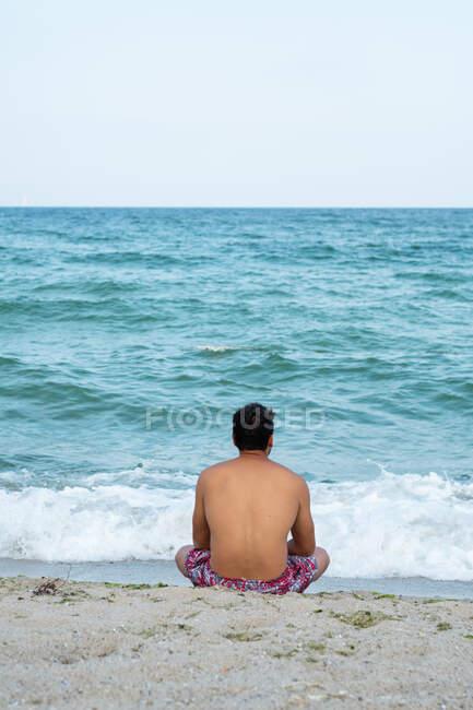 Вид сзади мужчины в шортах, сидящего на песчаном берегу возле великолепного моря, машущего в Тыленово, Болгария — стоковое фото