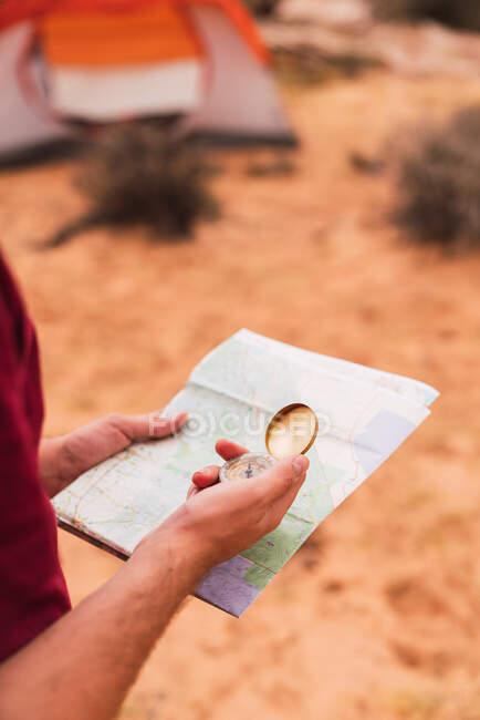 Чоловік, що тримає карту і компас, стоячи на невиразному тлі величної пустелі. — стокове фото
