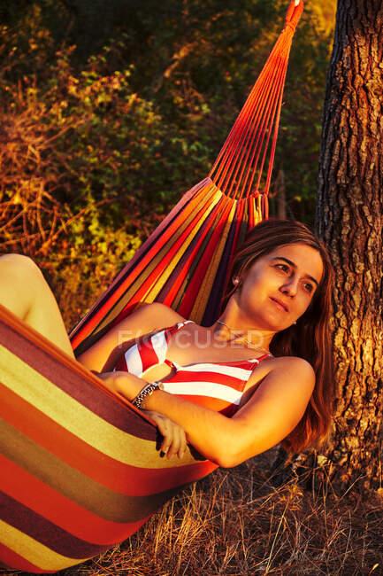 Женщина лежит в гамаке в солнечных лесах — стоковое фото