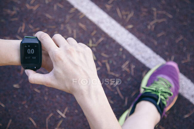 Crop shot from above of woman sitting on rubber racetrack and surfing smartphone — Stock Photo