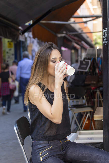 Attractive female in stylish outfit keeping eyes closed and enjoying fresh hot drink while sitting on chair on market — Stock Photo