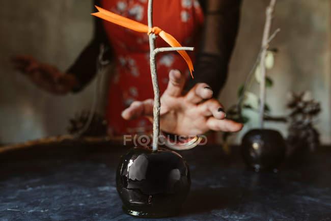 Femme main tenant noir pomme caramélisée pour halloween — Photo de stock