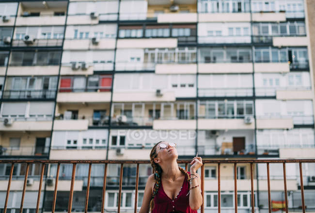 Stylish red-haired girl with braids and sunglasses smoking against residential building — Stock Photo