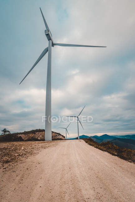 Row of modern windmills standing on side of narrow countryside road on cloudy day — Stock Photo