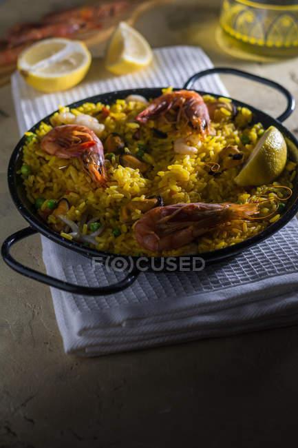 Marinera paella espagnole traditionnelle avec du riz, crevettes, calmars et moules dans la casserole sur la serviette — Photo de stock