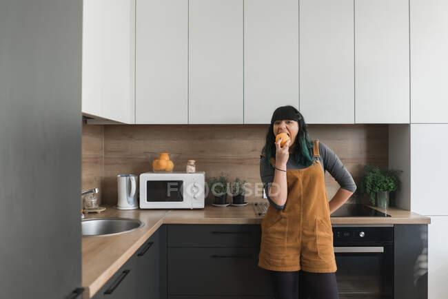 Muito jovem fêmea mordendo saborosa fruta fresca, enquanto em pé na cozinha moderna — Fotografia de Stock