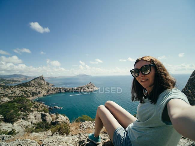 Donna che cattura selfie sulla scogliera con vista sul mare su priorità bassa — Foto stock