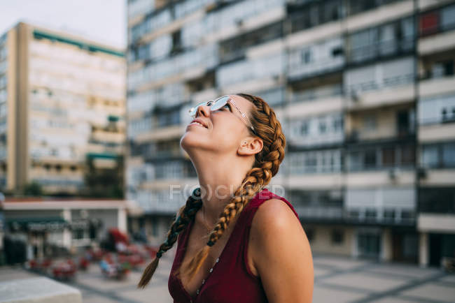 Smiling red-haired girl with braids and sunglasses walking in city — Stock Photo