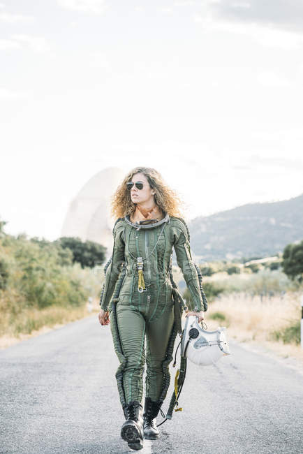 Female astronaut with curly hair walking along road in nature — Stock Photo