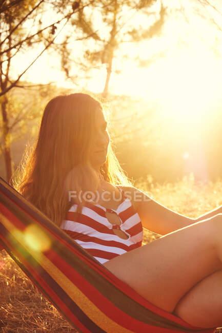Очаровательная женщина с длинными каштановыми волосами в красно-белом купальнике, лежащая в разноцветном гамаке на заднем плане с ярким солнцем и листвой — стоковое фото