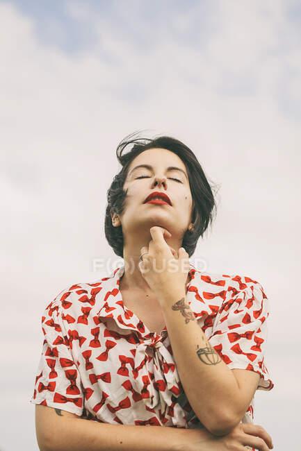 Dal basso vista di attraente donna bruna in camicia fantasia con tatuaggi sul braccio in piedi su sfondo di cielo nuvoloso con gli occhi chiusi — Foto stock