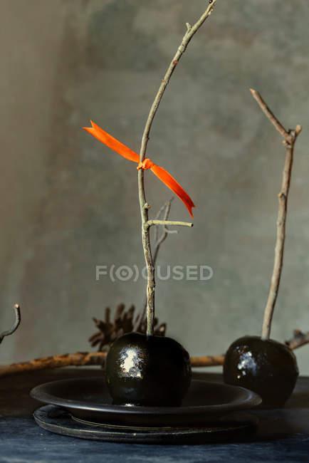 Pommes au caramel noirs avec des bâtons pour Halloween — Photo de stock