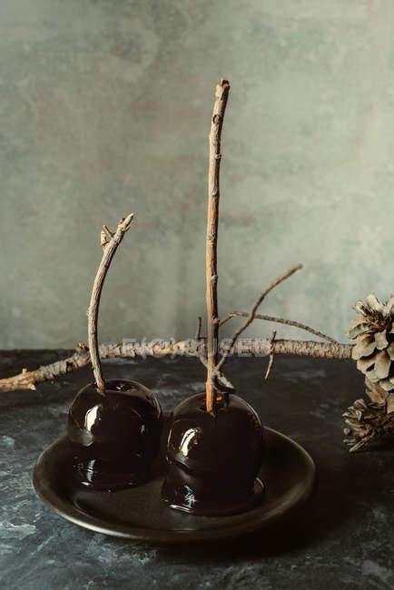 Pommes au caramel noirs avec des bâtons pour Halloween sur plaque noire — Photo de stock
