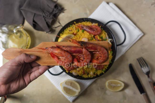Main de l'homme maintenant crevettes au dessus de la paella espagnole traditionnelle marinera avec riz, crevettes, calmars et moules en casserole — Photo de stock