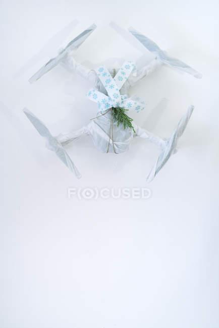Беспилотник, завернутый в рождественский подарок с элегантной лентой и еловой веткой на белом фоне — стоковое фото