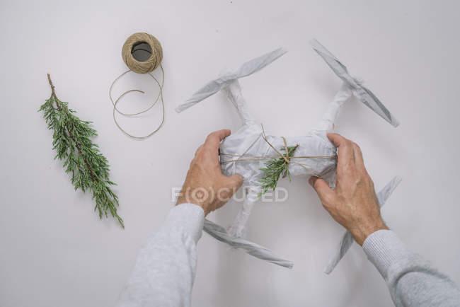 Masculinas mãos envolvendo o drone como presente de Natal com ramo de abeto e cordéis sobre fundo branco — Fotografia de Stock
