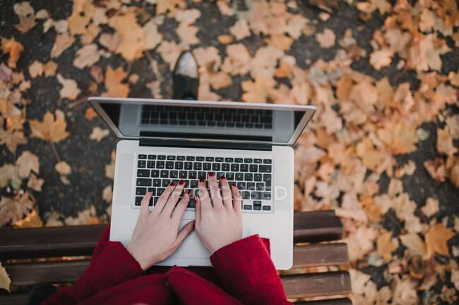 Жінка з ноутбуком сидить на лавці. — стокове фото