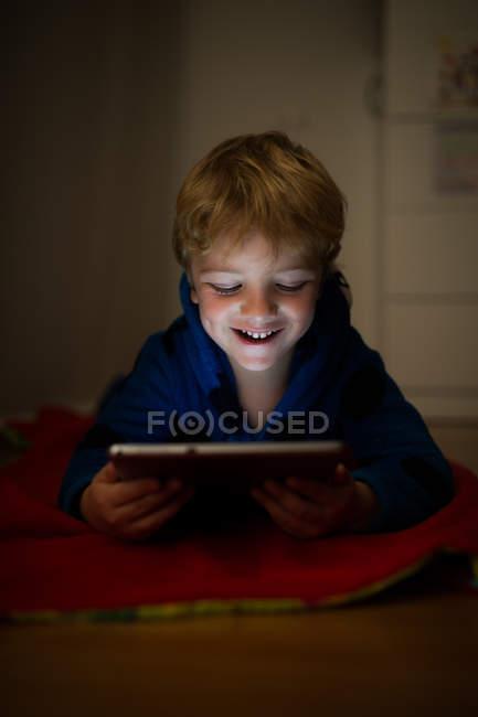 Fröhlicher kleiner Junge schaut Cartoons mit digitalem Tablet auf Holzboden — Stockfoto