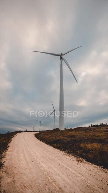 Ряд современных ветряных мельниц, стоящих на стороне узкой сельской дороги в пасмурный день — стоковое фото