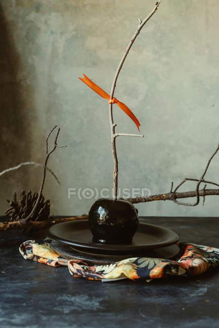 Pomme au caramel noir sur bâton pour halloween sur plaque — Photo de stock