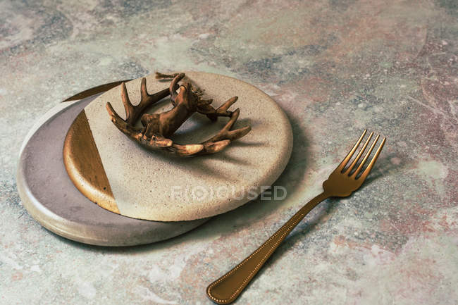 Christmas table set in white and gold colors decorated with figure of deer on concrete surface — Stock Photo