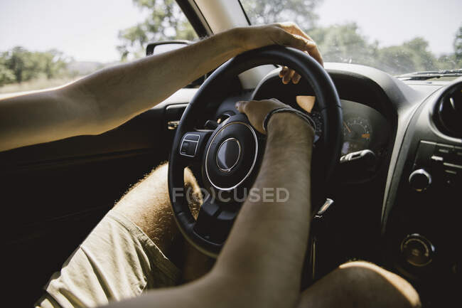 Unrecognizable man sitting on driver seat and holding hands on steering wheel while traveling through magnificent countryside by car — Stock Photo