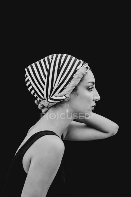 Молодая женщина в головной убор смотрит в камеру — стоковое фото