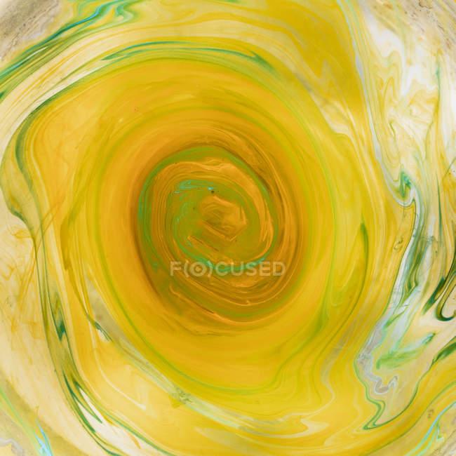 Swirls of dissolving yellow and green paint — Stock Photo