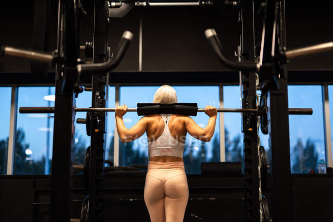 Young blond woman doing exercise with barbell in gym — Stock Photo