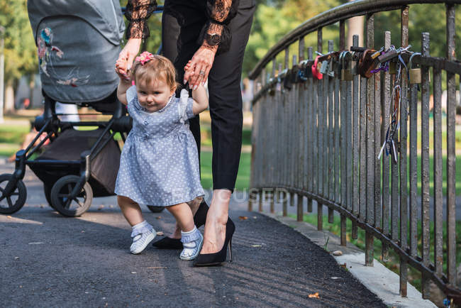 Woman in high-heeled shoes teaching cute baby girl to walk on small bridge in park — Stock Photo
