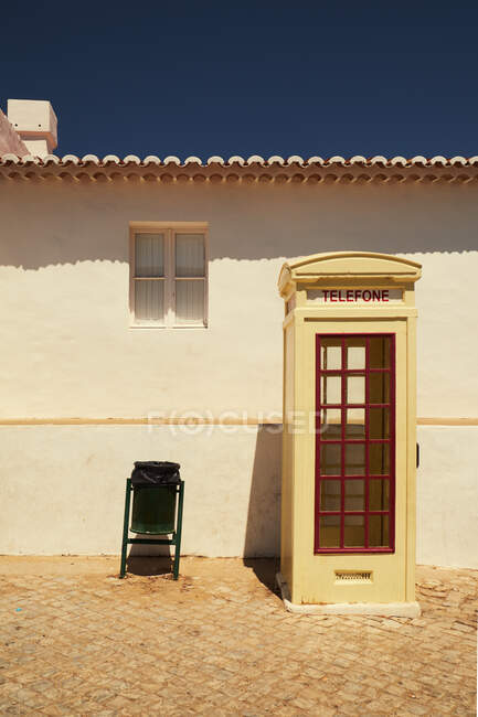 Vintage call-box with red wooden windows standing with green iron trash can at white building on blue sky background — Stock Photo