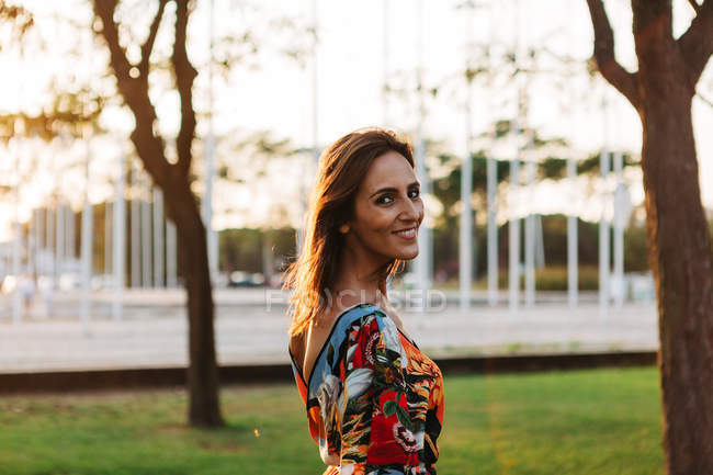 Brune élégante et souriante en robe debout dans un parc urbain et regardant la caméra — Photo de stock