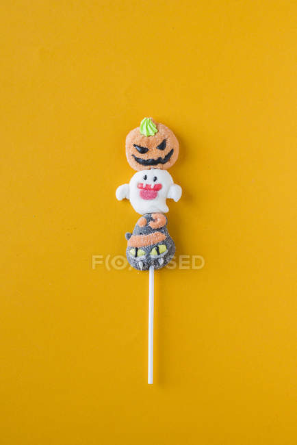 Хэллоуин конфеты на палочке на оранжевом фоне — стоковое фото