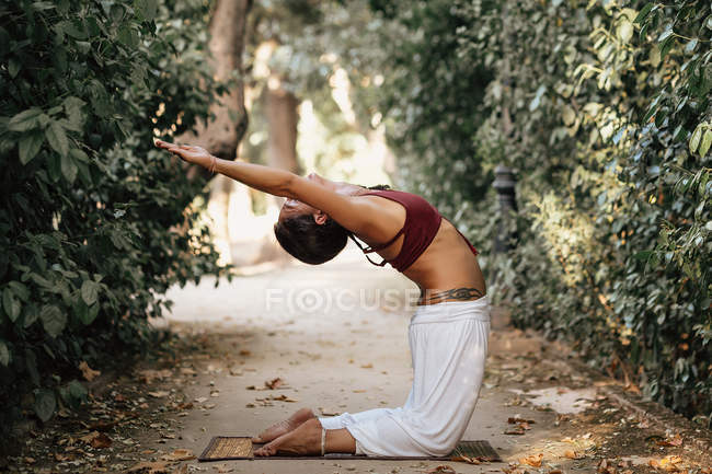 Slim woman bending back while doing yoga on alley in autumn park — Stock Photo