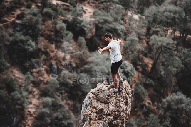 Marruecos - 5 de septiembre de 2018: Escalador parado en la cima de la roca con las manos separadas y mirando hacia abajo - foto de stock