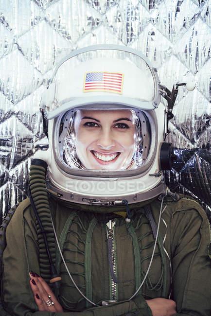 Улыбающаяся девушка в старом космическом шлеме и скафандре на фоне фольги — стоковое фото