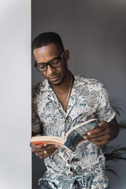 Casual black man in eyeglasses leaning on white wall near window and reading book — Stock Photo